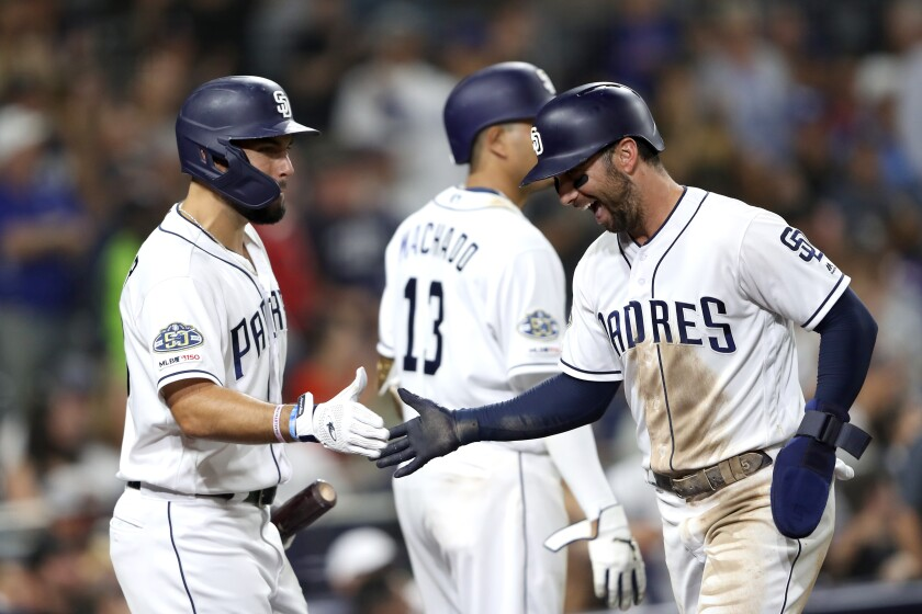 Greg Garcia, right, is congratulated by Eric Hosmer after scoring on a throwing error during the sixth inning of the Padres' 4-3 victory over the Dodgers on Monday at Petco Park.