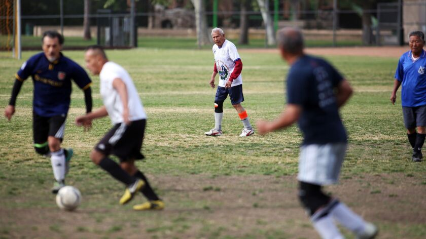 Marcos Gaitan, 90, center, keeps his eye on the ball during a soccer match at North Ranch Playfield.