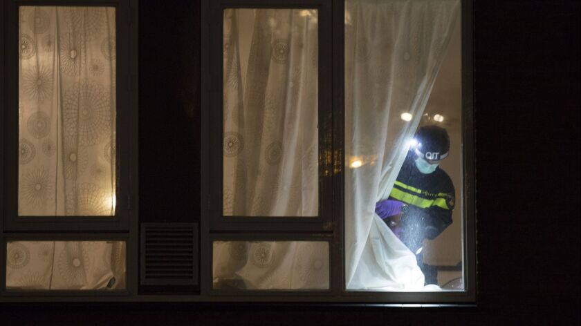 A forensics expert examines the house where a suspect in a deadly tram attack was arrested in Utrecht, Netherlands, on March 18.
