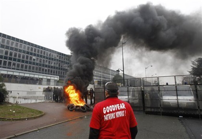 """FILE - In this March 7, 2013 file photo, a Goodyear worker wearing a tee shirt reading """"Goodyear, thug bosses"""" stands near burning tires, as police officers form a line during a demonstration against layoffs, at the Goodyear headquarters in Rueil Malmaison, west of Paris. Tensions - and even confro"""