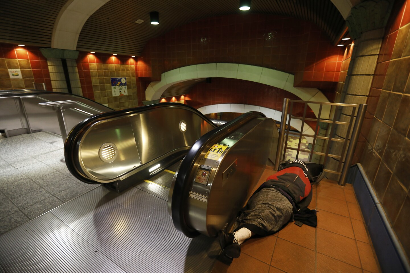 A person sleeps beside an escalator at the Hollywood/Vine Metro station. The 2018 Greater Los Angeles Homeless Count is tallying people around the city, including those sleeping near Metro stations and on trains.