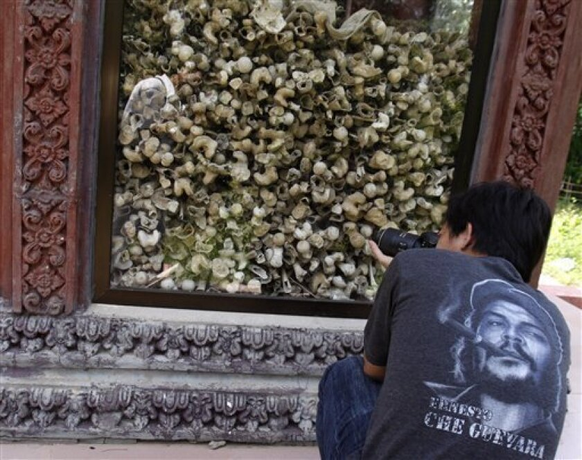 A Cambodian man photographs a small shrine with human bones and skulls, alleged victims of the Khmer Rouge, at Ampe Phnom village, Kampong Speu province, about 45 kilometers (28 miles) southwest of Phnom Penh, Cambodia, Sunday, July 5, 2009. (AP Photo/Heng Sinith)