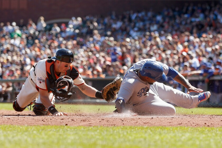 Dodgers second baseman Howie Kendrick slides safely past the tag of Giants catcher Trevor Brown to score on fielder's choice by teammate Andre Ethier in the third inning Thursday at AT&T Park.