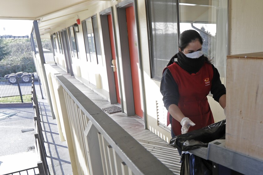 Housekeeping worker cleans a room at Econo Lodge in Kent, Wash.