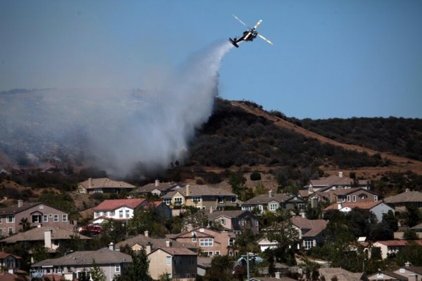 A helicopter douses a fire near Camarillo Springs that was fueled by Santa Ana winds and warm temperatures earlier this yeaar.
