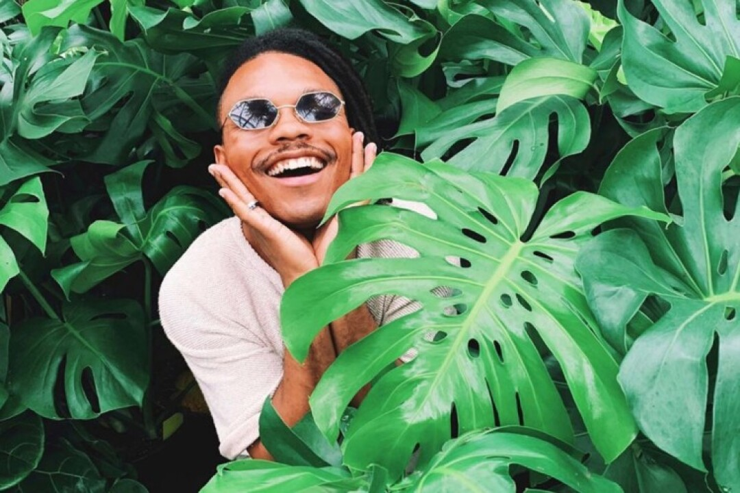 A smiling person wearing sunglasses and surrounded by monstera plant leaves.