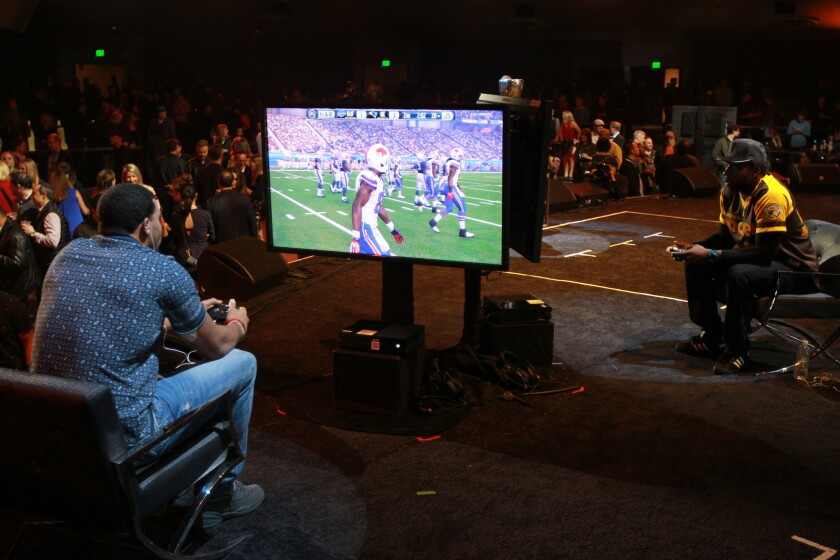"""Players compete in the """"Madden NFL"""" video game as part of a Super Bowl event in February."""