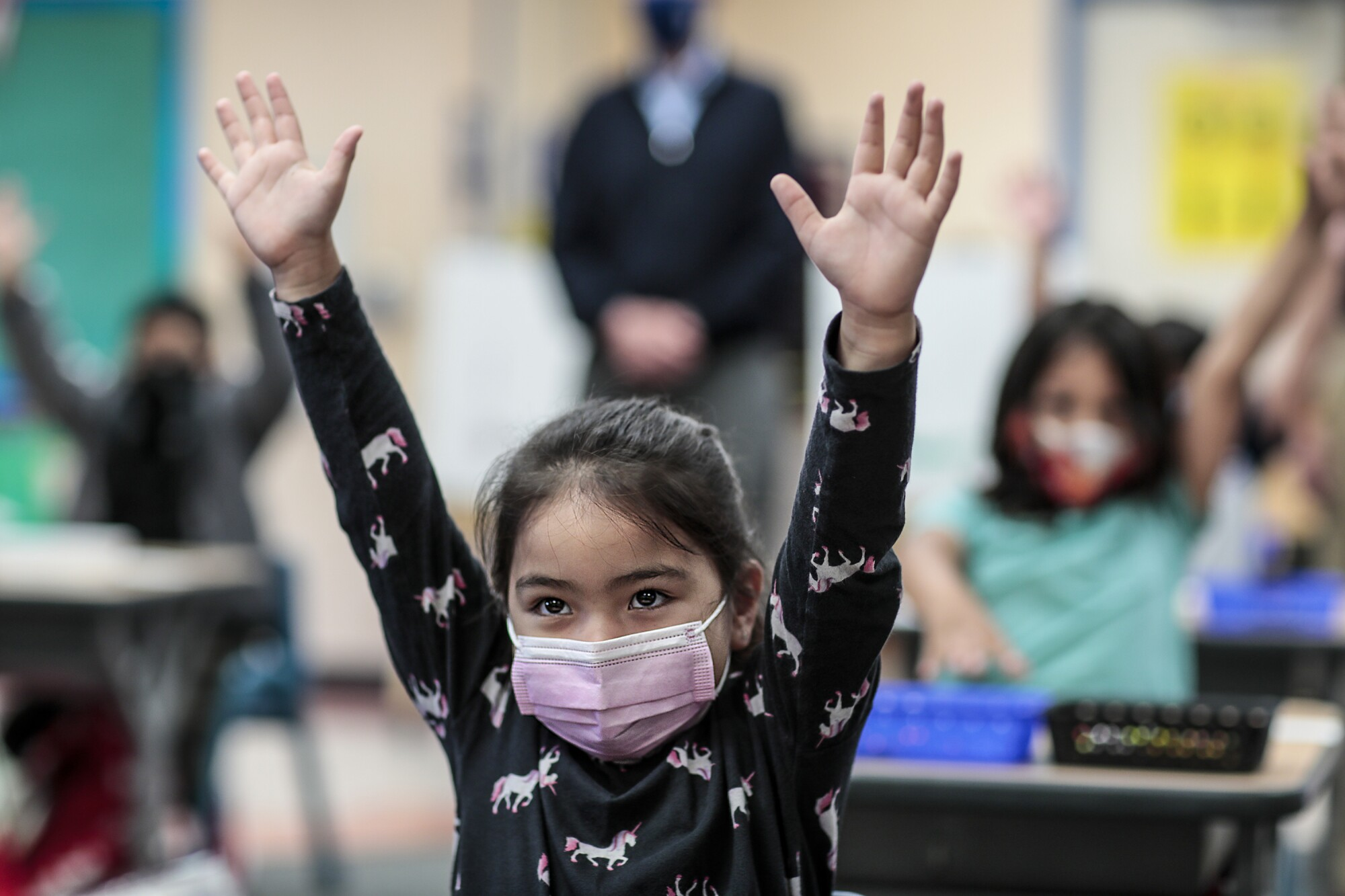 A girl in a pink face mask lifts both arms into the air.