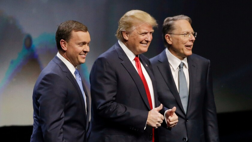 Republican presidential candidate Donald Trump is introduced by National Rifle Association executive director Chris W. Cox, left, and NRA executive vice president Wayne LaPierre as he takes the stage to speak at the NRA convention in Louisville, Ky. on May 20.