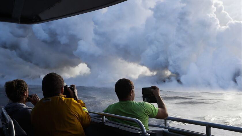 People take pictures as lava pours into the ocean, generating plumes of steam near Pahoa, Hawaii.