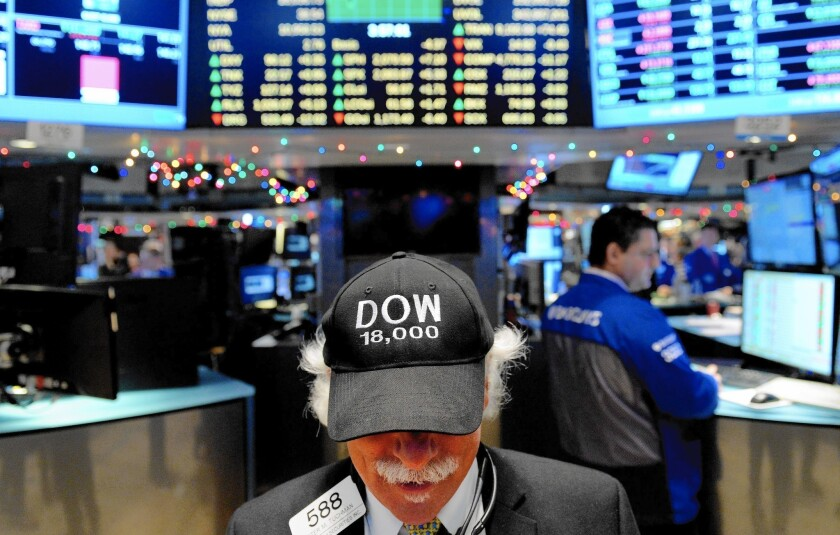"A trader wears a ""Dow 18,000"" hat on the floor of the New York Stock Exchange on Tuesday."