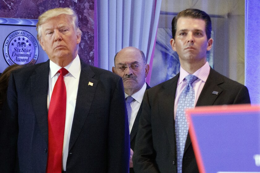 Allen Weisselberg stands behind Donald Trump and Donald Trump Jr. in the lobby of Trump Tower.