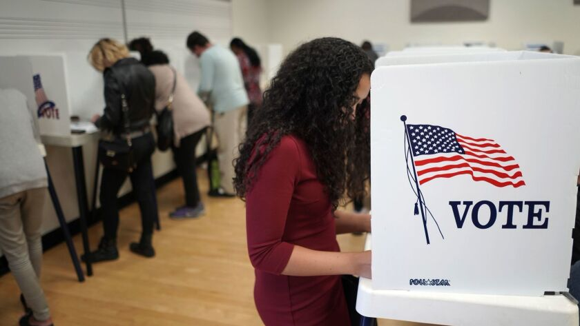 A woman marks her ballot at an early voting polling station at West Los Angeles College in Culver City on Sunday.