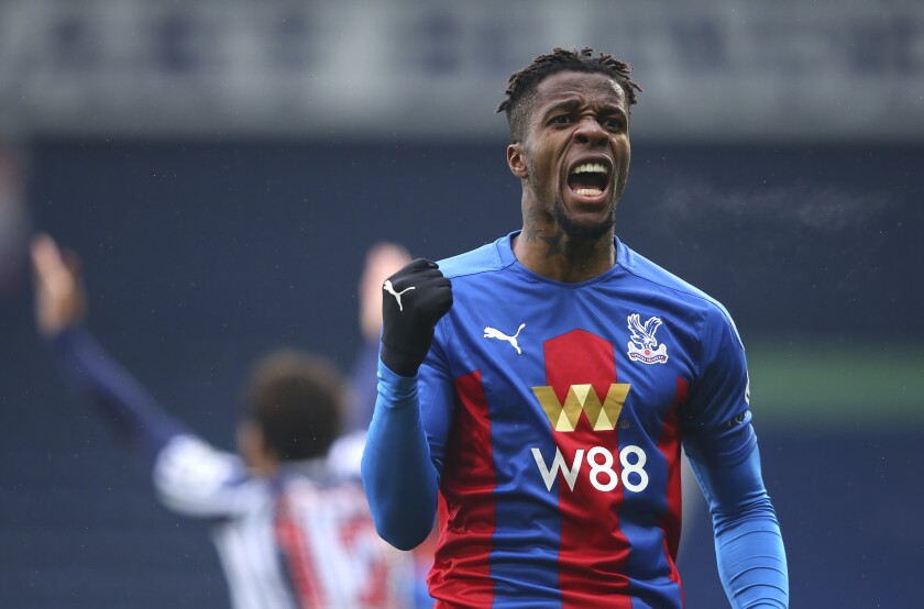 Crystal Palace's Wilfried Zaha celebrates after his shot is turned in by West Bromwich Albion's Darnell Furlong for the first goal during the English Premier League soccer match between West Bromwich Albion and Crystal Palace at the Hawthorns, West Bromwich, England, Sunday, Dec. 6, 2020. (Alex Livesey/Pool via AP)