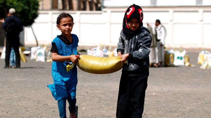 Children carry food aid distributed by a charity in Sana on June 7. Nearly a quarter of Yemen's popu