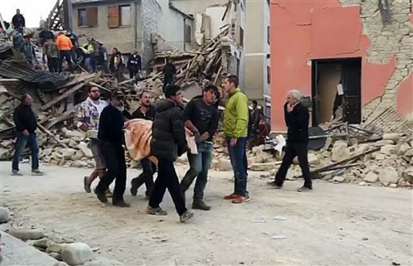 En esta imagen, tomada de un video, personas recuperan a una víctima de debajo de los escombros de un edificio en Amatrice, una localidad del centro de Italia sacudida por un sismo de magnitud 6,1,.