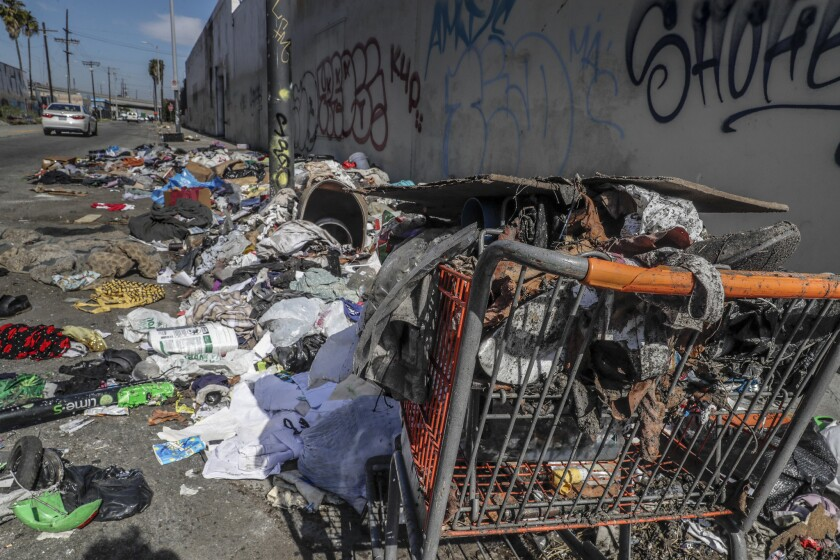 A shopping cart and piles of trash at the corner of Compton Avenue and East 16th Street.
