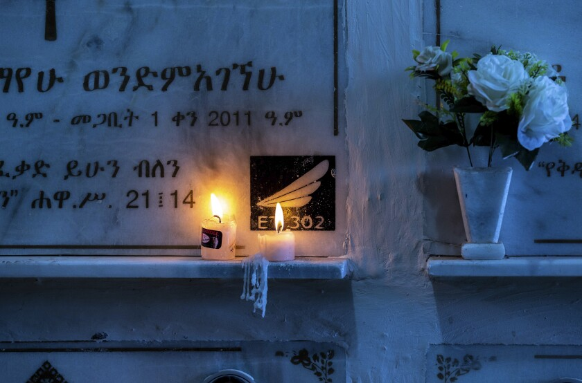 Candles are lit on a memorial wall during an anniversary memorial service to remember those who died when Ethiopian Airlines flight ET302, a Boeing 737 Max, crashed shortly after takeoff on March 10, 2019 killing all 157 on board, at the Holy Trinity Cathedral in Addis Ababa, Ethiopia Sunday, March 8, 2020. (AP Photo/Mulugeta Ayene)