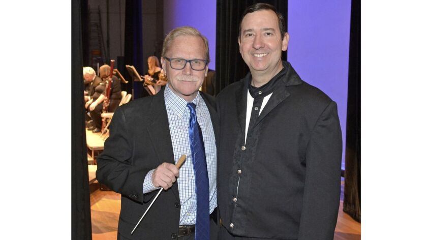 Guest conductor, Los Angeles Times columnist Chris Erskine, left, getting last minute tips in the wi