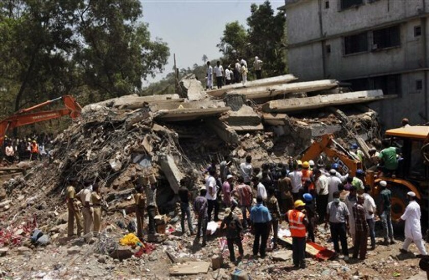 People gather around a heap of debris at the site of a building collapsed as a rescue operation continues on the outskirts of Mumbai, India, Friday, April 5, 2013. A half-finished building that was being constructed illegally in a suburb of India's financial capital collapsed, killing 35 people and injuring more than 50 others, police said Friday. (AP Photo/Rajanish Kakade)