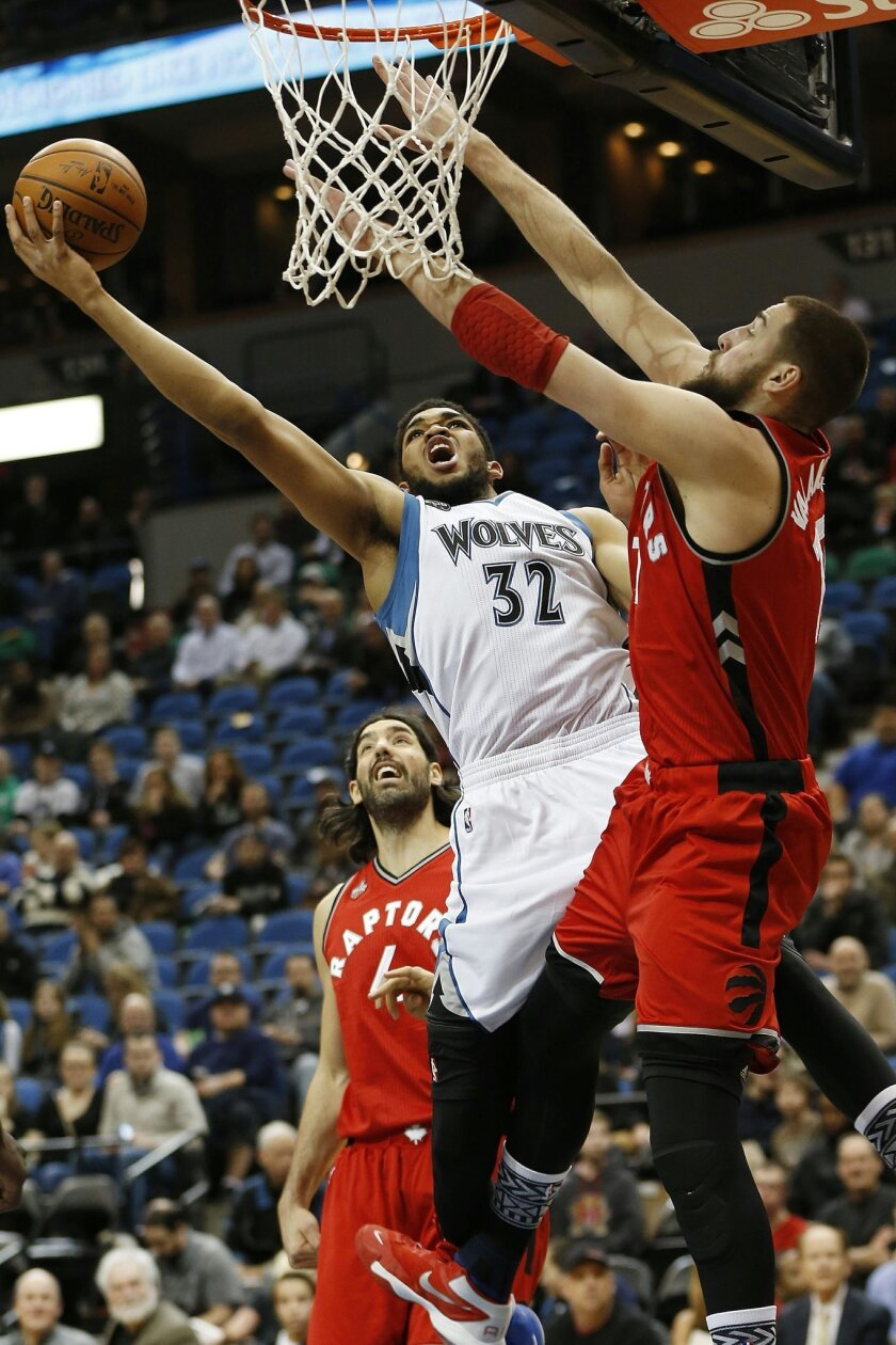 Minnesota Timberwolves center Karl-Anthony Towns (32) goes up to the basket against Toronto Raptors center Jonas Valanciunas (17) in the first half of an NBA basketball game Wednesday, Feb. 10, 2016 in Minneapolis. (AP Photo/Stacy Bengs)