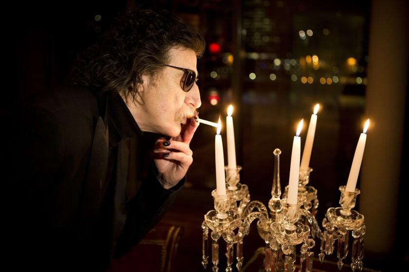 La leyenda del rock argentino Charly Garcia prende un cigarro con una vela antes de una entrevista en Buenos Aires, Argentina en una fotografía de archivo del 14 de agosto de 2013. Garcia ingresó a un hospital para una revisión el 28 de diciembre de 2016 informaron su abogada y su productor.