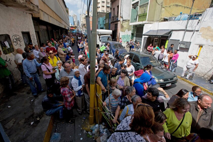 People line up outside a supermarket in Caracas, Venezuela, to buy price-regulated toilet paper made available for sale by the government on Jan. 22, 2016.