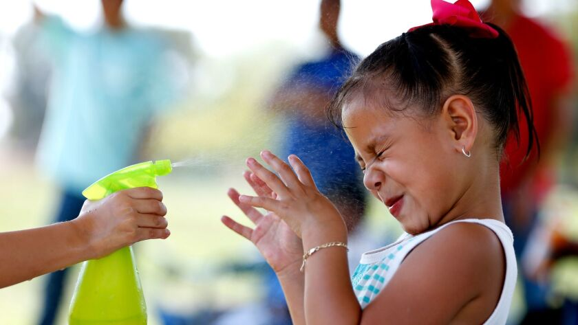 Samantha Tlaxcalteco, 4, left, of Winnetka, sprays her friend Cynthia Torres, 5, of Canoga Park, with cold water at the Balboa Sports Center in Encino.