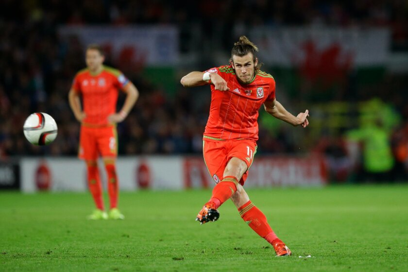 FILE - In this Tuesday, Oct. 13, 2015 file photo, Wales' Gareth Bale hits a freekick during the Euro 2016 Group B soccer match between Wales and Andorra at Cardiff City stadium in Cardiff. (AP Photo/Matt Dunham, File)