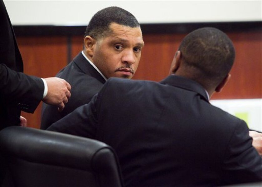 "Defendant Mark Goudeau talks with one of his attorneys, Rodrick Carter before the start of opening arguments during the trial for the ""Baseline Killer"" crimes at the Superior Court Central Court Building in downtown Phoenix on Monday, June 6, 2011. (AP Photo/Michael Schennum, Pool)"