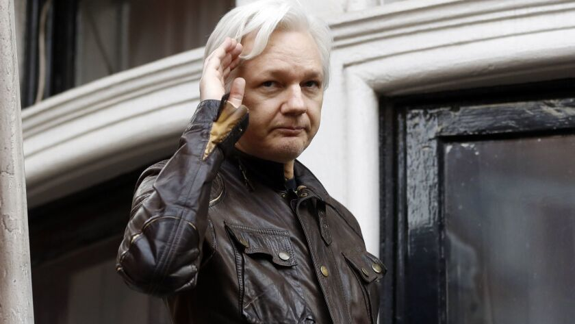 WikiLeaks founder Julian Assange greets supporters from a balcony of the Ecuadorean Embassy in London in 2013.