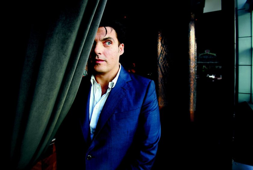 """Joe Wright, the director of the new movie """"Hanna,"""" peeks out from behind a curtain as he talked  at the Se San Diego Hotel Thursday.   Peggy Peattie/San Diego Union-Tribune"""