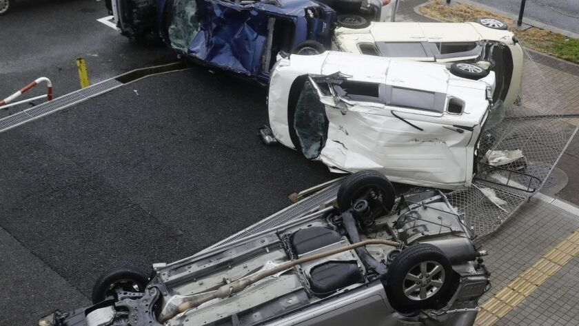 Overturned cars are seen on street following a powerful typhoon in Osaka, western Japan, Tuesday, Se