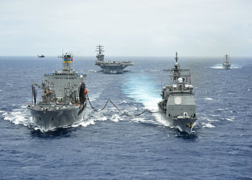 """The San Diego cruiser Princeton, right, gets a load of biofuel from oiler Henry J. Kaiser during the Navy's """"great green fleet"""" demonstration Wednesday off Hawaii. The aircraft carrier Nimitz and destroyer Chung-Hoon, in formation, also took on biofuel during the display, which was held during the"""