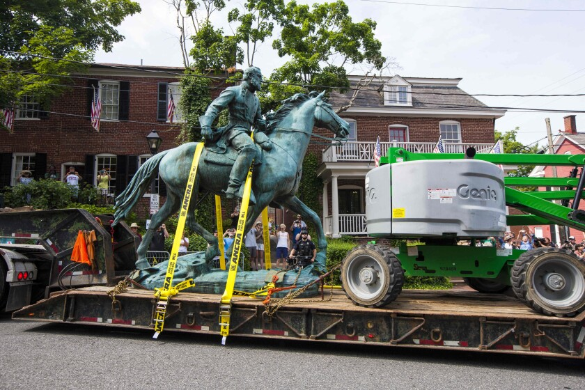 """The monument of Stonewall Jackson is hauled away on Saturday, July 10, 2021 in Charlottesville, Va. The removal of the Lee and Jackson statues comes nearly four years after violence erupted at the infamous """"Unite the Right"""" rally. (AP Photo/John C. Clark)"""