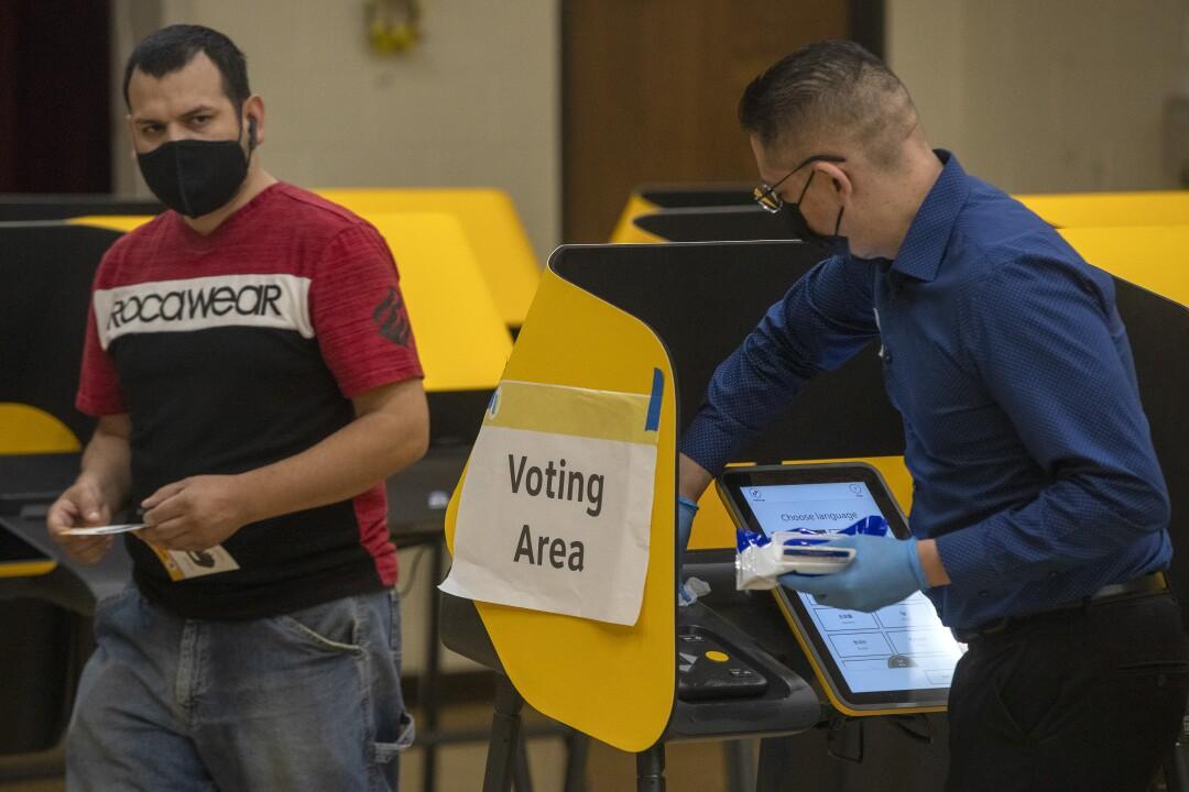 Ein Wahlhelfer desinfiziert einen Wahlautomaten, nachdem die Wähler ihre Stimme abgegeben haben
