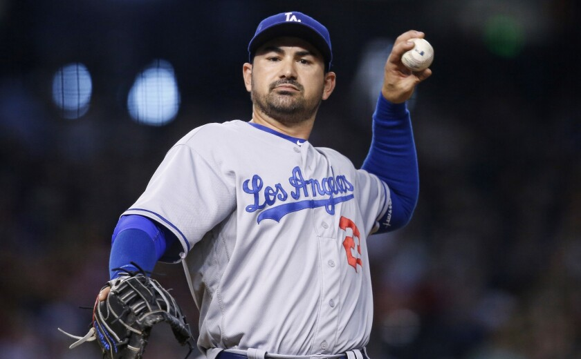 Dodgers first baseman Adrian Gonzalez throws a baseball to fans on June 15.