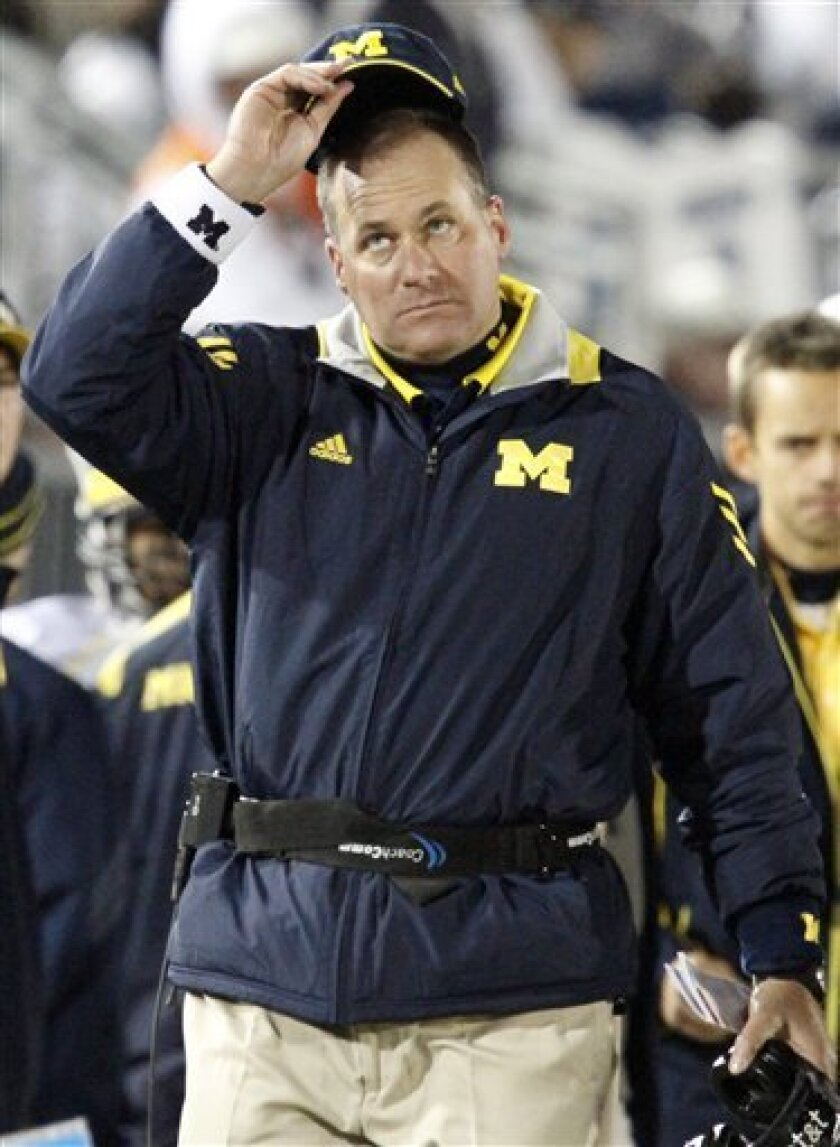 Michigan coach Rich Rodriguez looks at the scoreboard during the fourth quarter of a 41-31 loss to Penn State in an NCAA college football game in State College, Pa., Saturday, Oct. 30, 2010. (AP Photo/Gene J. Puskar)