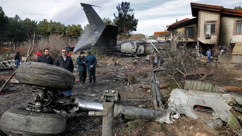 Iranian rescue personnel and security work at the site of a Boeing 707 cargo plane crash, at Fath Airport on Monday.