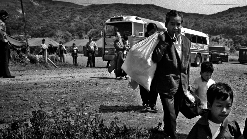 JUNE 12, 1975. CAMP PENDLETON, CA. Vietnamese refugees file off a Greyhound at the Camp Talega rel