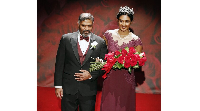Princess Rucha S. Kadam, of La Canada High School, with her father Shailesh, walk onto the stage to