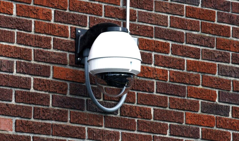 A security camera hangs on the side of the Skyline School in Portland, Ore.