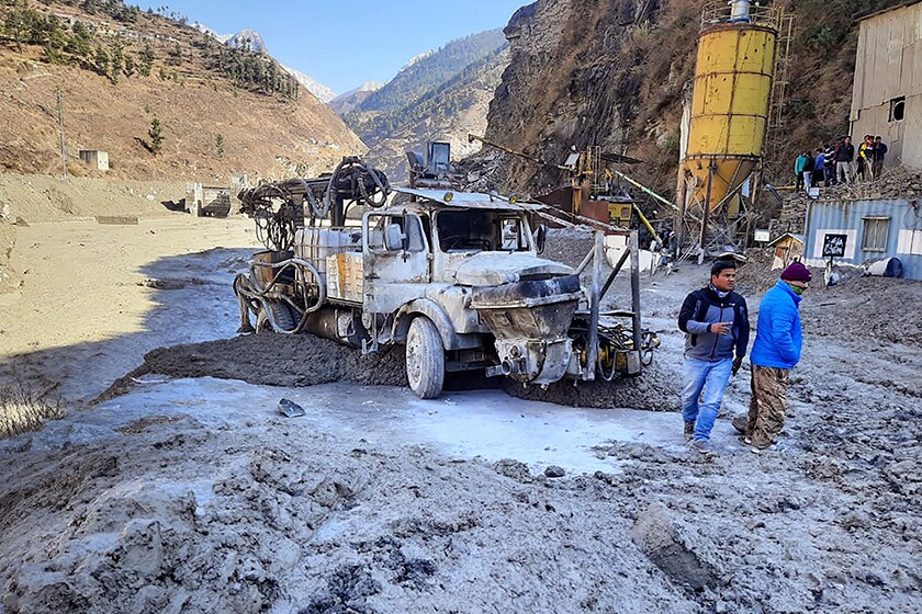 Two men stand near a damaged truck amid hilly terrain.