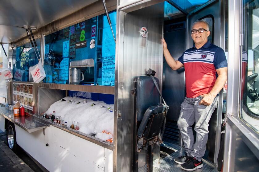 Mariscos Jaliscos owner Raul Ortega stands in the doorway of his food truck.