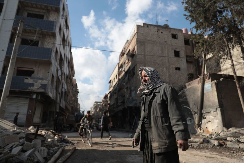 Syrian Abu Khaled looks at the rubble of his destroyed house in the rebel-held town of Douma, on the eastern outskirts of Damascus, on December 30, 2016.