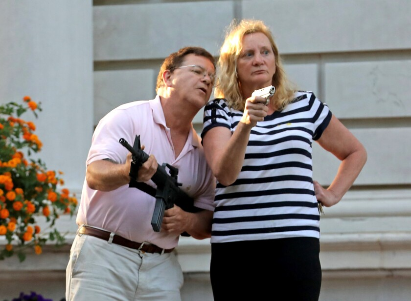 Mark and Patricia McCloskey point guns at protestors marching by their St. Louis mansion in June.