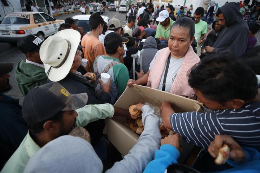 Migrantes hondureños se preparan para caminar otro tramo de territorio mexicano rumbo a su objetivo principal, Estados Unidos, en un campamento instalado en el jardín Hidalgo de Tapachula, en el estado de Chiapas (Mérxico) hoy, lunes 22 de octubre de 2018. EFE