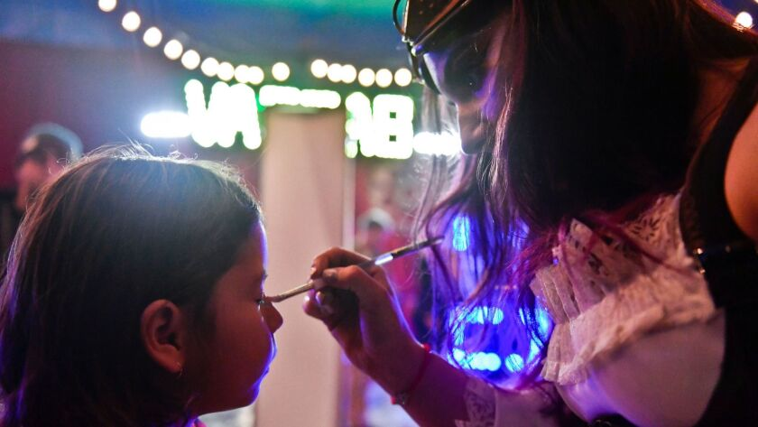 Sidni Politzer, 5, left, has her face painted by Annabel Bachliyski at intermission during a Sunday evening show at Circus Vargas. Bachliyski is also a performer for Circus Vargas.