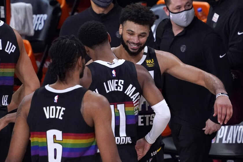 Denver Nuggets' Jamal Murray, right, celebrates with Monte Morris (11) after an NBA conference semifinal playoff basketball against the Los Angeles Clippers game Sunday, Sept. 13, 2020, in Lake Buena Vista, Fla. The Nuggets won 111-98. (AP Photo/Mark J. Terrill)