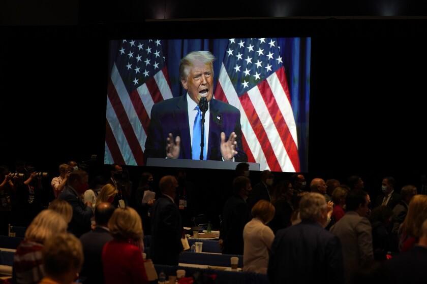 ARCHIVO - En imagen de archivo del lunes 4 de agosto de 2020, una pantalla muestra al entonces presidente estadounidense Donald Trump mientras ofrece un discurso, durante el primer día de la convención del Comité Nacional Republicano en Charlotte, Carolina del Norte. (AP Foto/Evan Vucci, archivo)